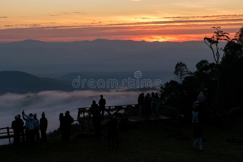 Silhouette of many tourists watching sun rise. CHIANG MAI, THAILAND - DEC 04, 2016 Silhouette of many tourists watching sun rise with selfie smart pole on stock photography