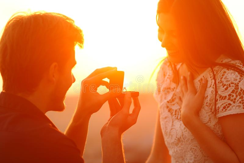 Silhouette of a marriage proposal at sunset royalty free stock photos