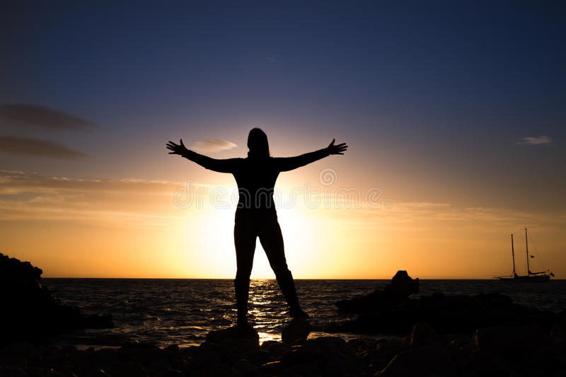Silhouette of mature woman with open arms stock photos