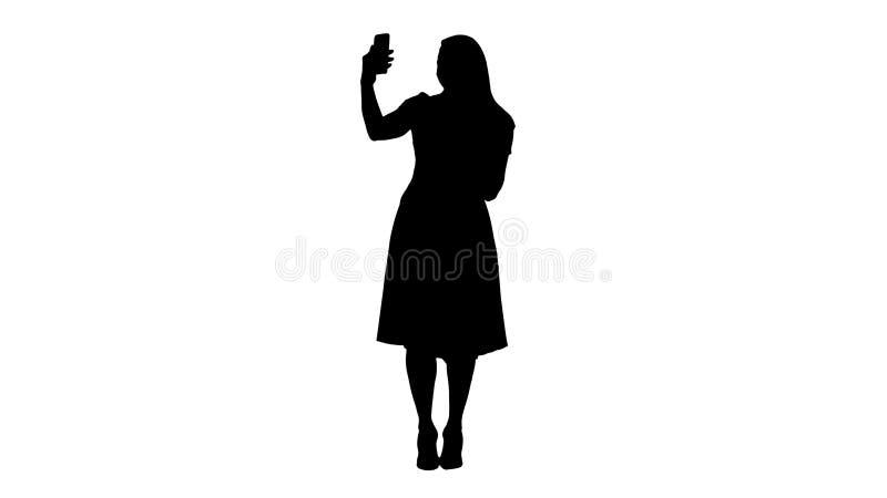 Silhouette Mature woman wearing light pink dress making selfie. royalty free stock photography