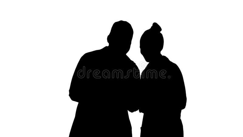 Silhouette Medical team looking at phone together. royalty free stock photo