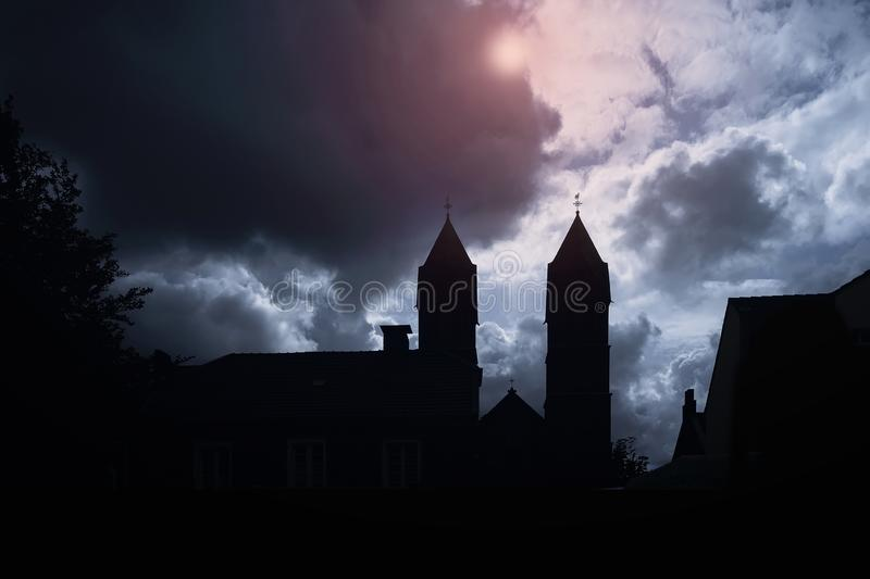 Silhouette of medieval castle and the cathedral church, night over dark sky background with the full moon royalty free stock photography