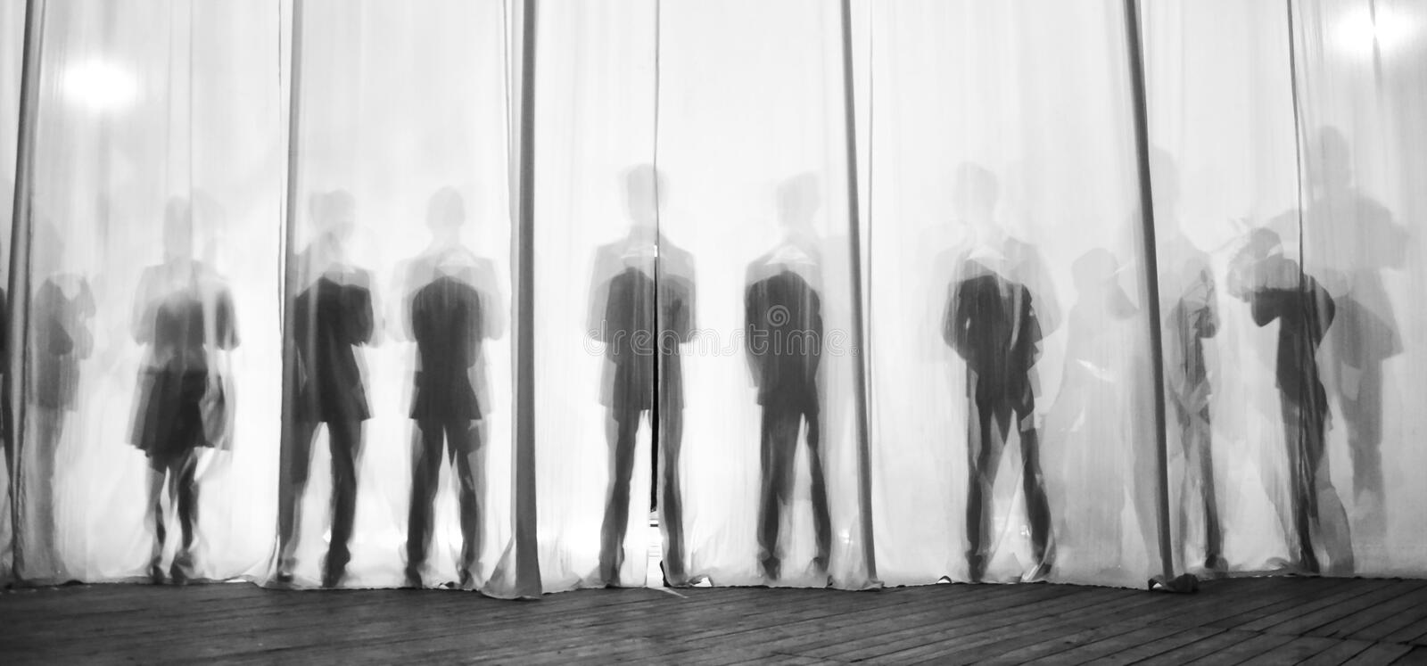 The silhouette of the men behind the curtain in the theater on stage, the shadow behind the scenes is similar to the white and bla. Ck piano keys stock photo
