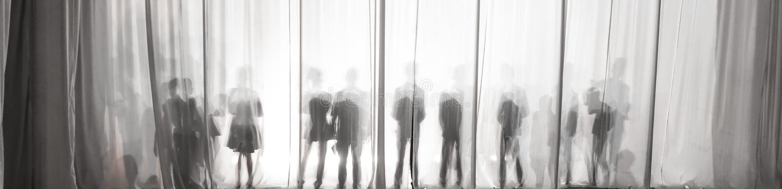 The silhouette of the men behind the curtain in the theater on stage, the shadow behind the scenes is similar to the white and bla. Ck piano keys stock photography
