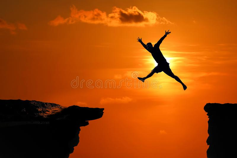 Silhouette of Men are jumped between high cliff at a red sky sunset stock photo