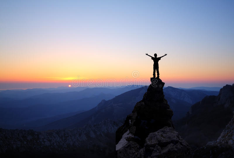 Silhouette of men on top of the mountain stock images