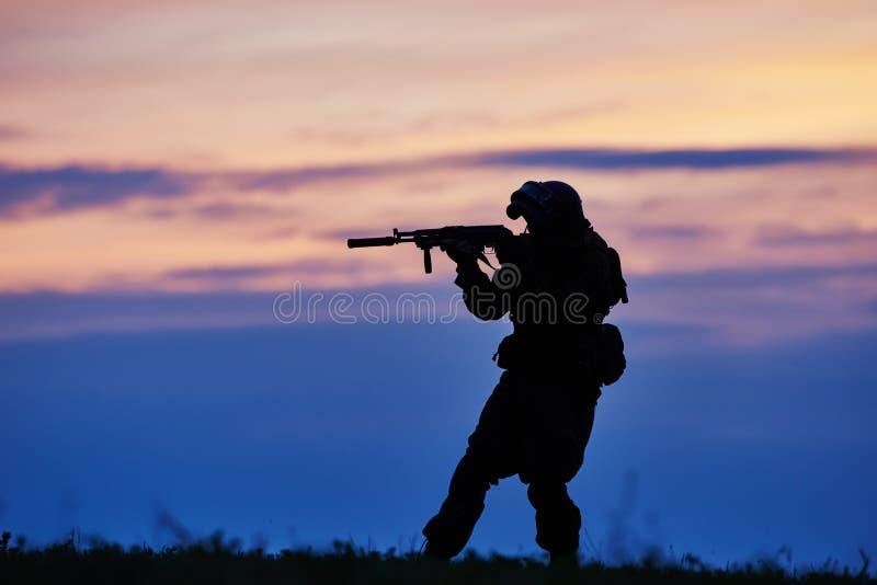 Silhouette militaire de soldat avec la mitrailleuse photographie stock