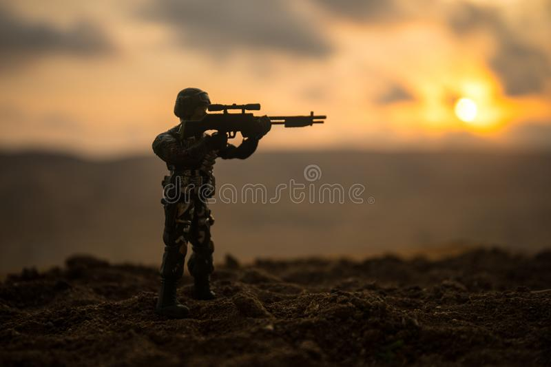Silhouette of military soldier or officer with weapons at sunset. shot, holding gun, colorful sky, mountain, background. Decoratio stock image