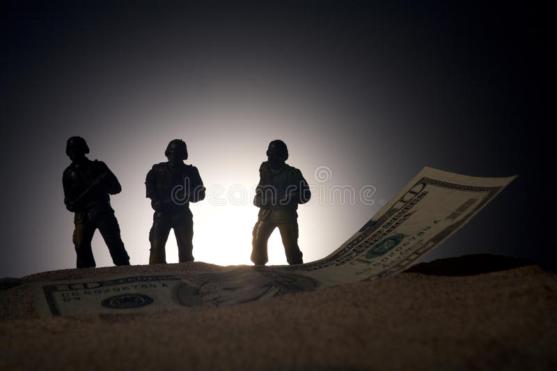 Silhouette of military soldiers on money background royalty free stock image