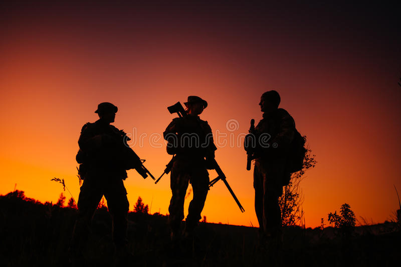 Silhouette of military soldiers with weapons at night. shot, holding gun, colorful sky. . royalty free stock images