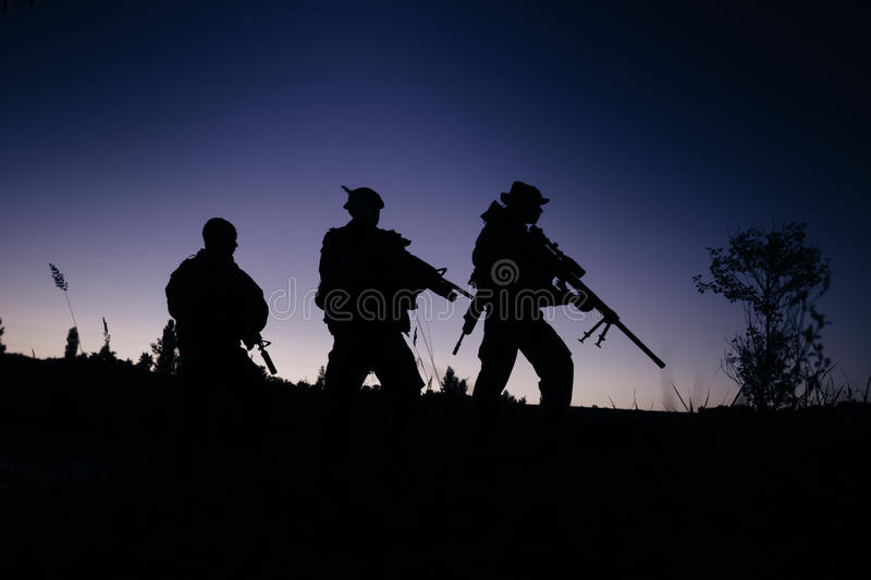 Silhouette of military soldiers with weapons at night. shot, holding gun, colorful sky. . royalty free stock image