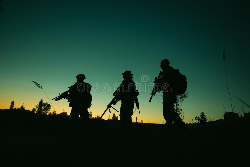 Silhouette of military soldiers with weapons at night. shot, holding gun, colorful sky. . stock images