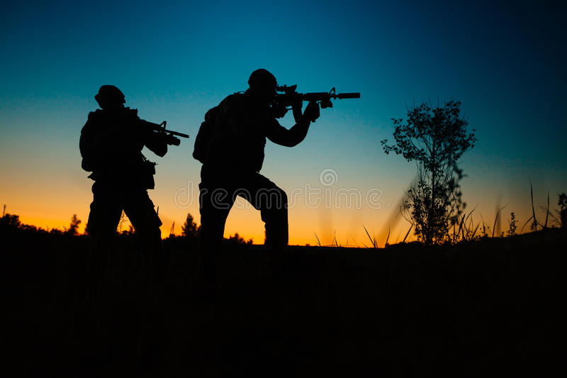 Silhouette of military soldiers with weapons at night. shot, holding gun, colorful sky. . royalty free stock photography