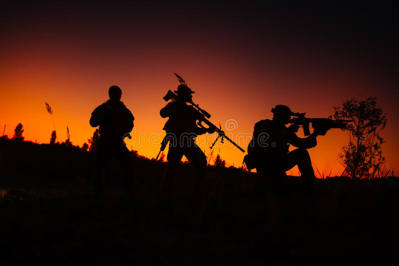 Silhouette of military soldiers with weapons at night. shot, holding gun, colorful sky. . stock photo