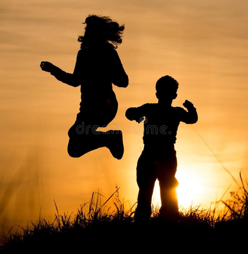 Silhouette of Mom and son in the rays of sunset royalty free stock images