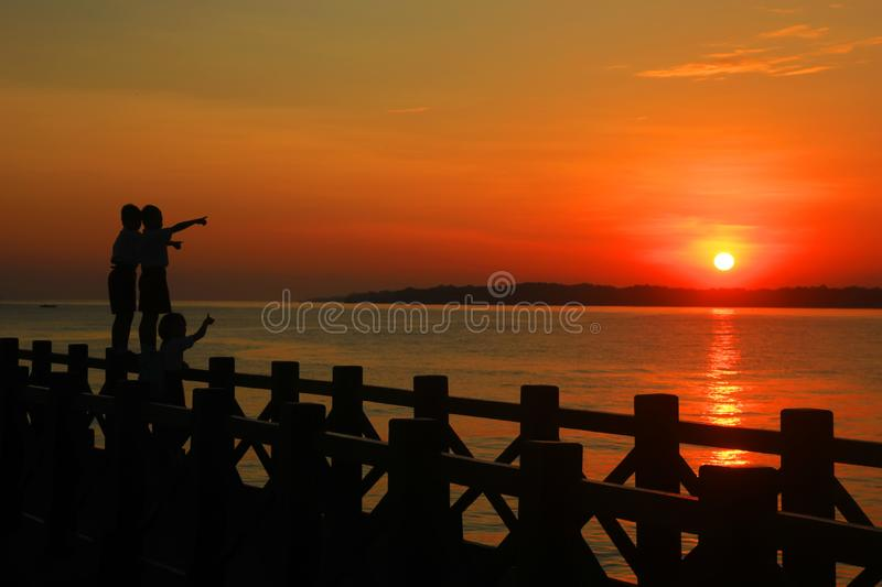 probolinggo indonesia. July 6, 2016. Silhouette of children playing welcoming sunrise on the beach royalty free stock images