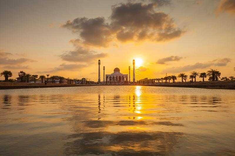 A silhouette of a mosque reflection on water at sunset timing. A silhouette of a mosque reflection on water at sunset under colorful vivid color sky located at stock photo