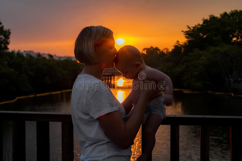 Silhouette of mother and baby on sunset on the bridge stock photos