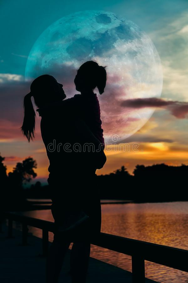 Silhouette of mother and daughter enjoying view. stock photos