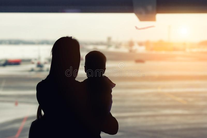 Silhouette of mother holding on hands little toddler boy with window of airport on background. Departure and arrival. Single. Mother with child emigration. Mom royalty free stock photography
