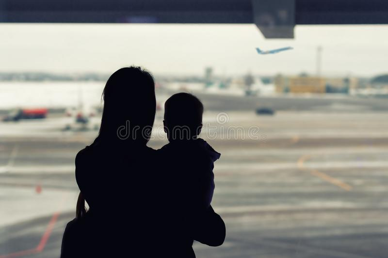 Silhouette of mother holding on hands little toddler boy with window of airport on background. Departure and arrival. Single. Mother with child emigration. Mom stock photos