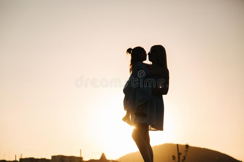 Silhouette of mother and little daughter. Summer sunset stock photo