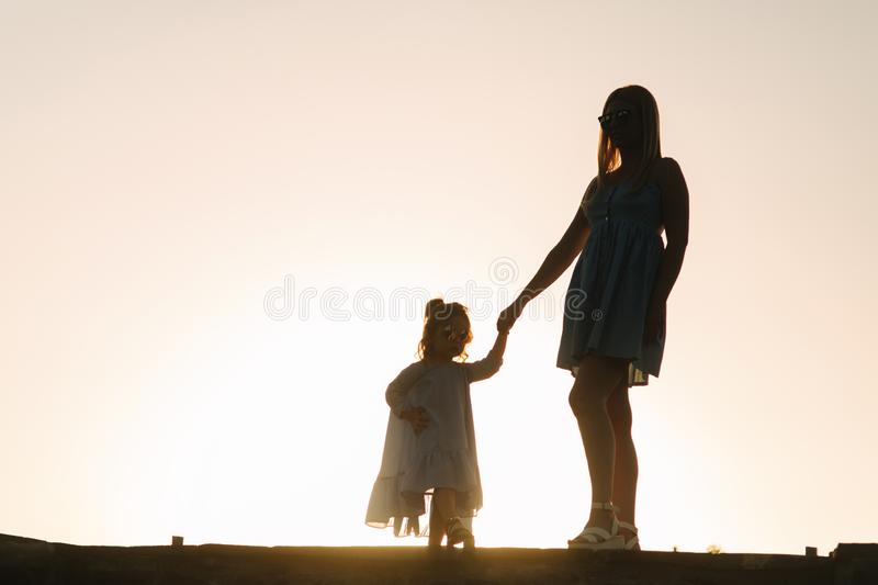 Silhouette of mother and little daughter. Summer sunset royalty free stock images