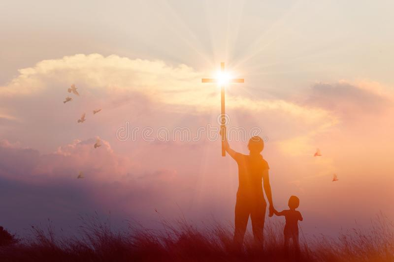 Silhouette of mother and son christian prayers raising cross while praying to the Jesus on sunset background. Worship concept royalty free stock images