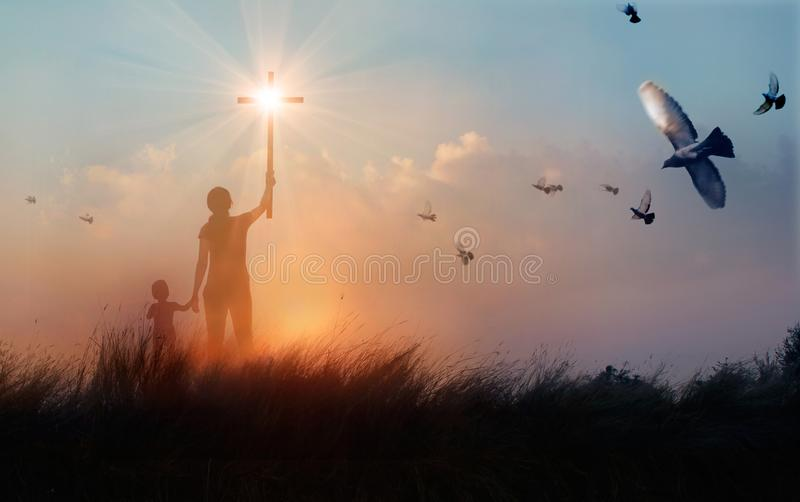 Silhouette of mother and son christian prayers raising cross while praying to the Jesus on sunset background, worship concept royalty free stock images