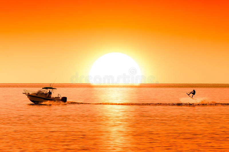 Silhouette of motor boat and wakeboarder at sunset performing trick. Silhouette of motor boat and wakeboarder at sunset performing crazy trick stock images