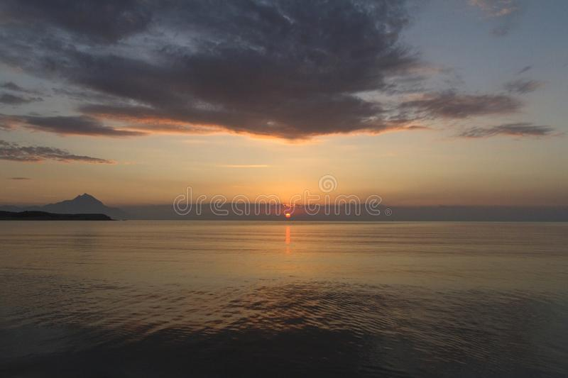 Silhouette of mount Athos at sunrise or sunset with light rays and sea panorama in Greece royalty free stock photo
