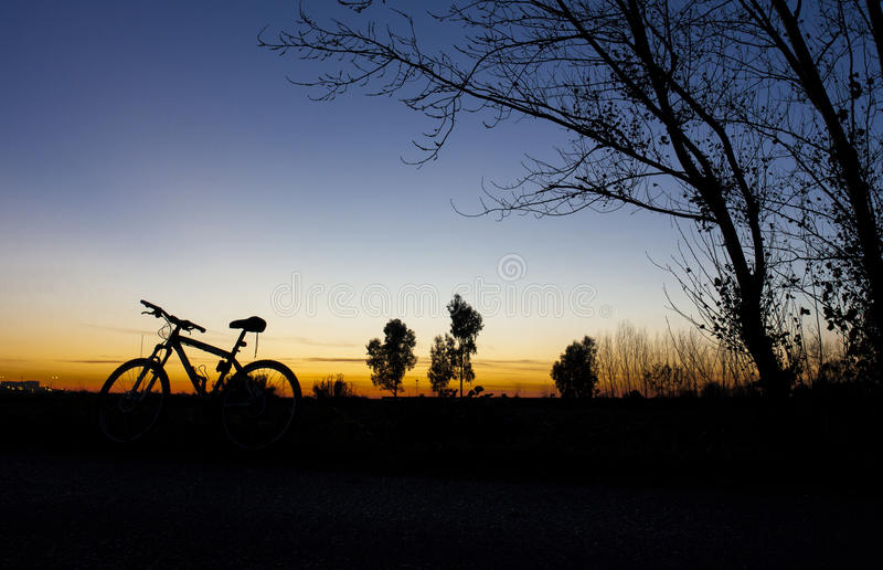 Silhouette of Mountain bike at sunset on blue sky. Silhouette of Mountain bike at sunset under tree on blue sky stock photos