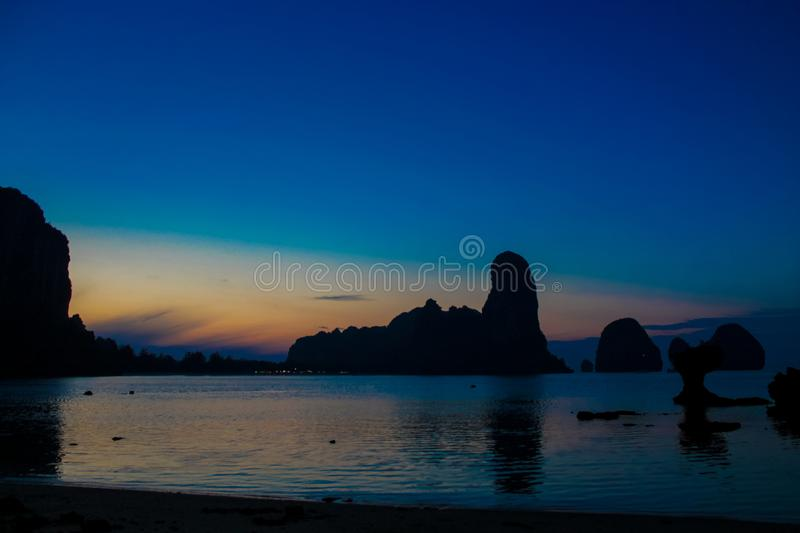 Silhouette of mountain cliff at blue sunrise on sea beach resort in Thailand, Krabi, Railey and Tonsai. Silhouette of mountain cliff at sunset on sea beach stock photography