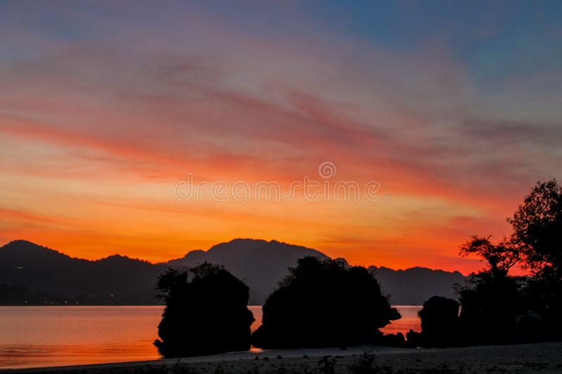 Silhouette of mountain cliff at orange pink sunset on sea beach resort in Thailand, Krabi, Railey and Tonsai stock photos