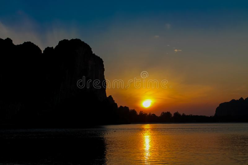 Silhouette of mountain cliff at sunrise on sea beach resort in Thailand, Krabi, Railey and Tonsai. Silhouette of mountain cliff at sunset on sea beach resort in stock photos