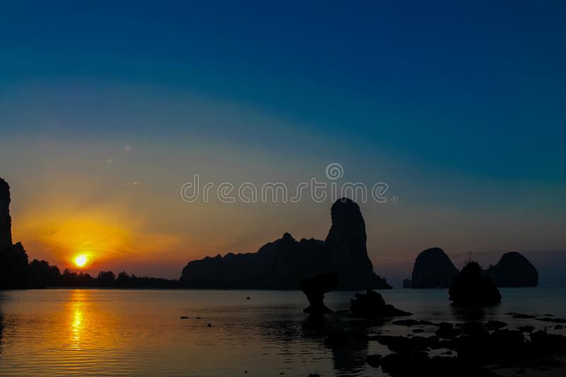 Silhouette of mountain cliff at sunrise on sea beach resort in Thailand, Krabi, Railey and Tonsai stock photography