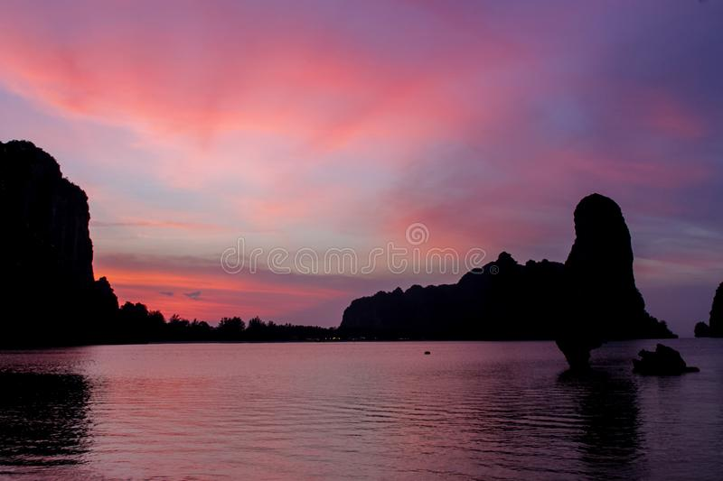 Silhouette of mountain cliff at violet sunrise on sea beach resort in Thailand, Krabi, Railey and Tonsai royalty free stock image