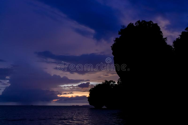 Silhouette of mountain cliff at violet sunset on sea beach resort in Thailand, Krabi, Railey and Tonsai stock photography