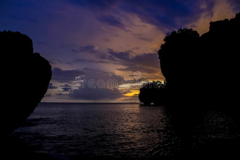Silhouette of mountain cliff at violet sunset on sea beach resort in Thailand, Krabi, Railey and Tonsai royalty free stock photos