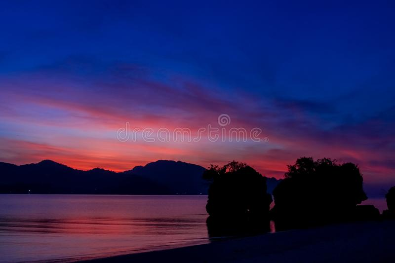 Silhouette of mountain cliff at violet sunset on sea beach resort in Thailand, Krabi, Railey and Tonsai stock photo