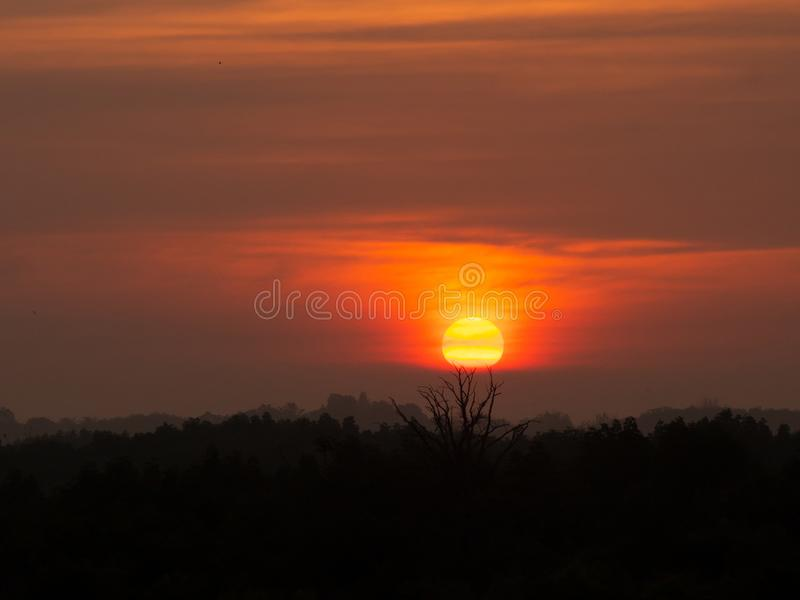 Silhouette mountain hill with big sun at sunrise sunset. Orange and yellow sky and clouds stock photo