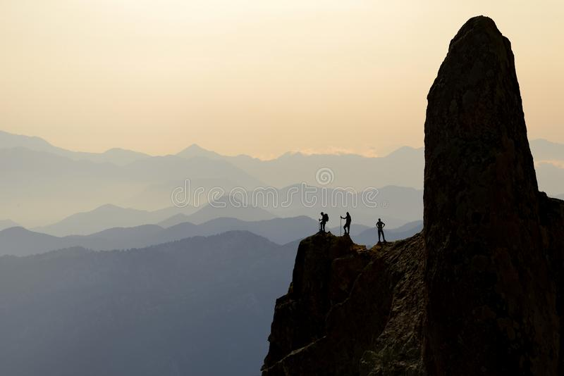 Adventurers on mountain peak. The silhouette of a mountain peak with a group of adventurers looking down in the valley royalty free stock photo