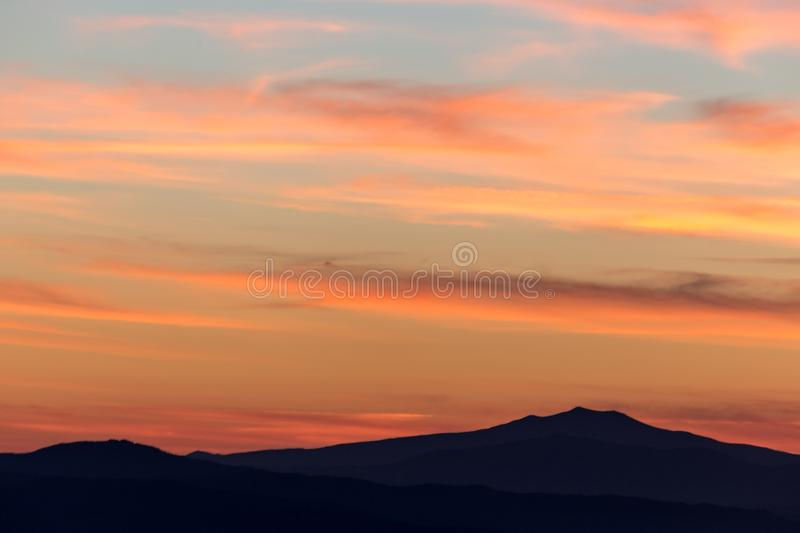A silhouette of a mountain peak at sunset, under a big sky with. Beautiful, striped red clouds stock image