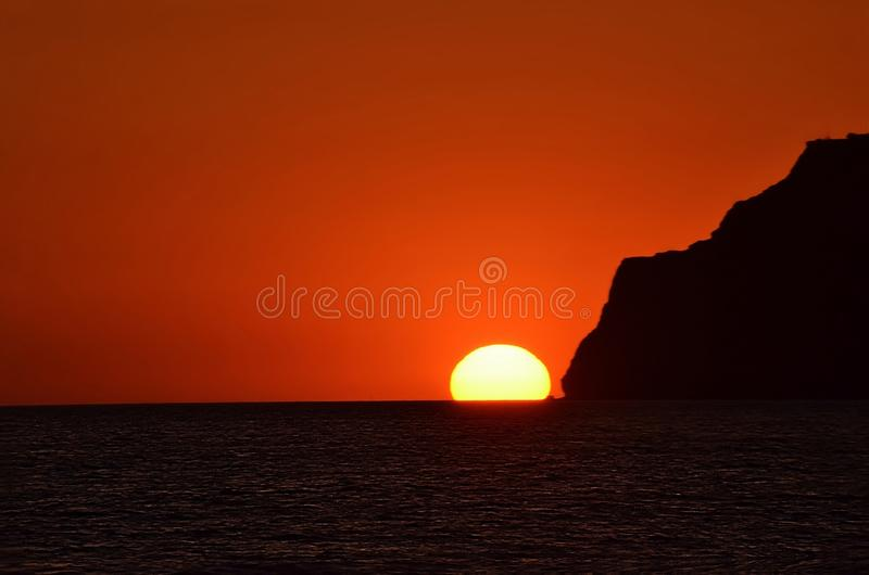 The silhouette of the mountain, the smooth descent of the solar disk into the sea. The sunset in the sea, the mountain coast of Crimea, the silhouette of the stock photo