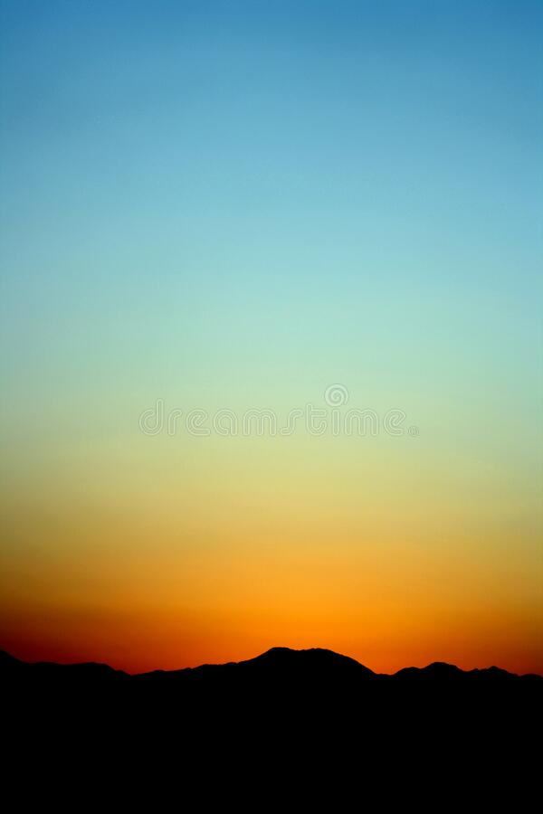 Silhouette of Mountain Under Orange and Blue Sky during Sunset royalty free stock photos