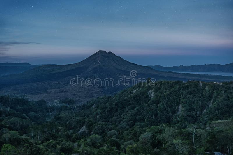 Silhouette of the mountain volcano Batur on background night sky with stars. Presented to active travelers royalty free stock photo