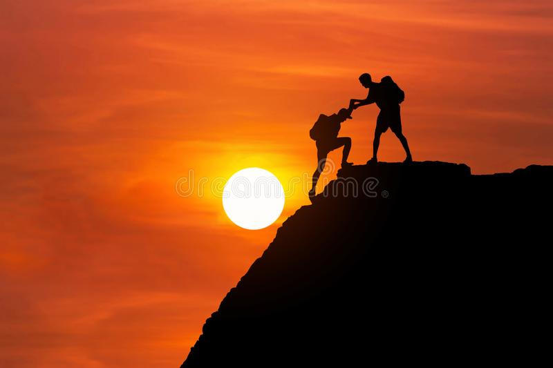 Silhouette mountaineer gives helping hand his friend to climb high cliff mountain together. Teamwork success concept royalty free stock photos