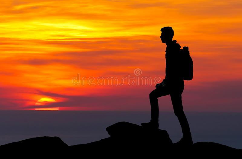 Silhouette of a mountaineer standing on the top stock photos