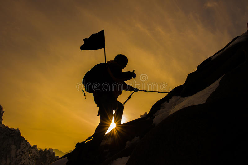 Silhouette of mountaineer and sunset. stock photos