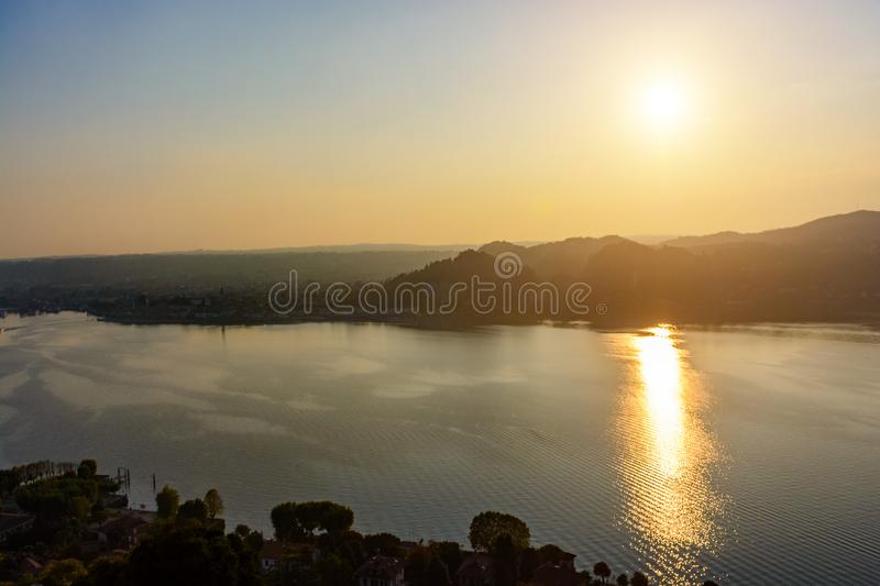 Silhouette of the mountains and the town of Arona in Italy at sunset and water. royalty free stock images